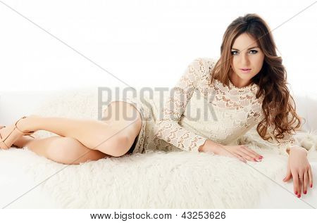 The beautiful woman. The woman in a white dress on a white sofa. isolated on white background