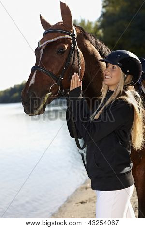 Riverside portrait of horsewoman holding bridle, caressing horse, smiling happy.