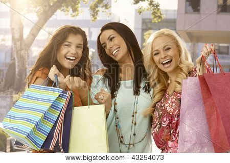 Attractive female friends holding shopping bags, smiling happy outdoors.