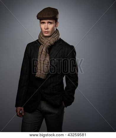 Young man in brown jacket wearing cap and scarf isolated on grey background