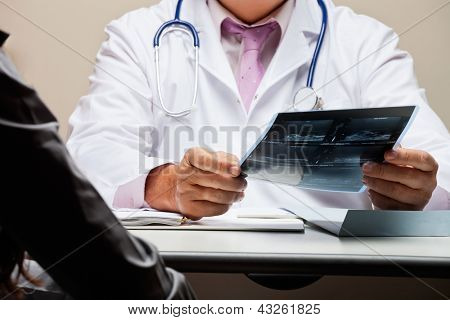 Midsection of male radiologist at desk holding patient's x-ray