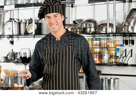 Portrait of happy male chef holding glass of red wine at commercial kitchen