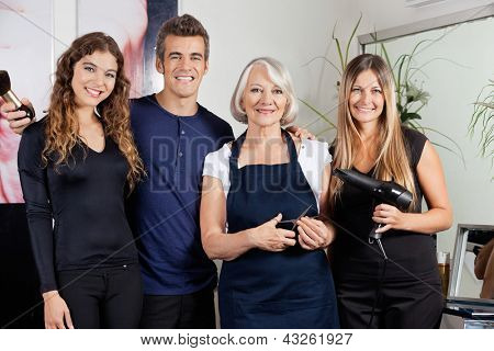 Portrait of confident hairdressers standing together at salon