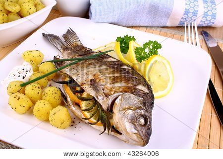 Grilled Fish Served With Potatoes, Sauce And Lemon
