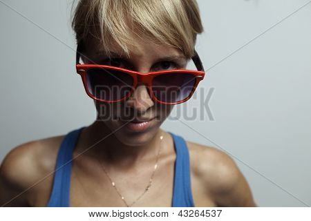 Close up portrait of a young woman with big glasses looking to a camera. DOF, Focus on a glasses