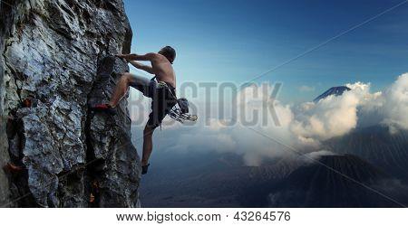 Joven escalada pared rocosa natural con volcanes en el fondo