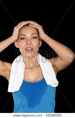 Fitness woman sweating. Beautiful sport girl with towel and sweat looking at camera tired, exhausted and sweaty after gym exercise. Multiracial fit female fitness model isolated on black background.