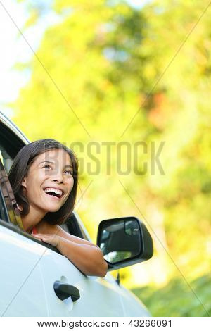 Car woman on road trip looking out of window smiling happy. Beautiful multicultural Asian Caucasian woman.