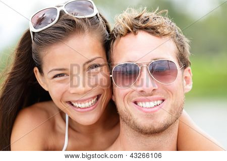 Happy young beach couple closeup portrait outdoors in sun. Young people wearing sunglasses eyewear. Joyful interracial couple, Asian woman, Caucasian man.