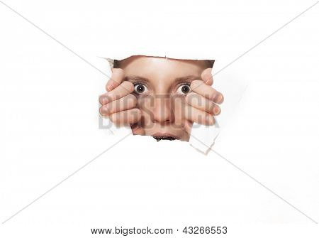 Young woman looking through torn paper hole