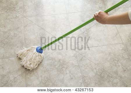 young woman scrubbing floor with a mop