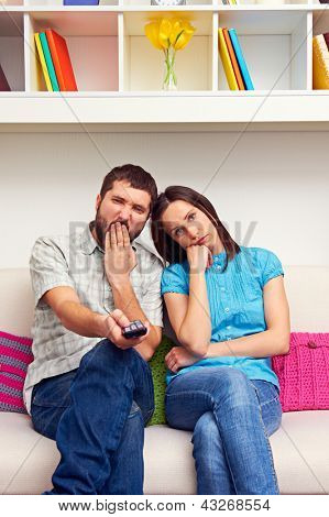 bored couple sitting on the sofa and watching TV