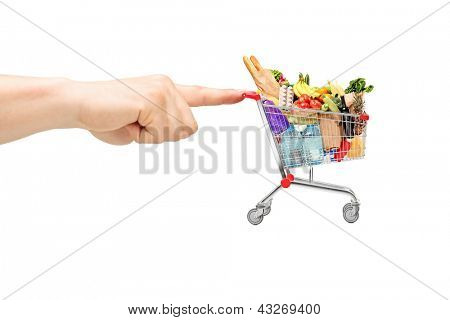 Finger pushing a shopping cart full of food products, isolated on white background