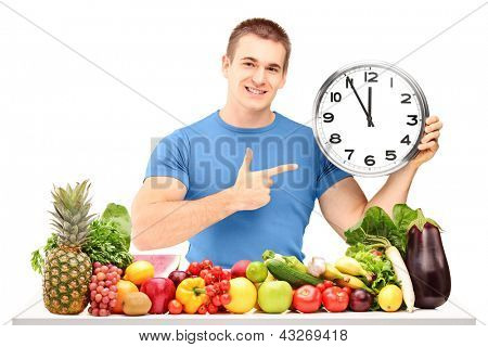 Young man holding a clock and posing with a pile of fruits and vegetables, isolated on white background