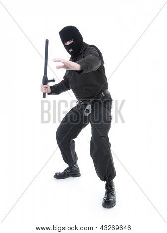 Anti-terrorist police guy wearing black uniform and black mask holding firmly police club in one hand ready for action, shot on white