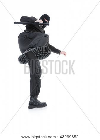 Anti-terrorist police guy wearing black uniform and black mask making a side kick, shot on white
