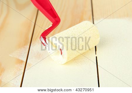 Paint roller brush with white paint, on wooden background