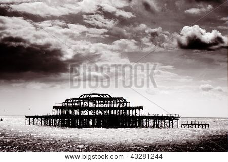 Remains Of Brighton Pier Left Standing In Sea With Dark Clouds, England, Uk