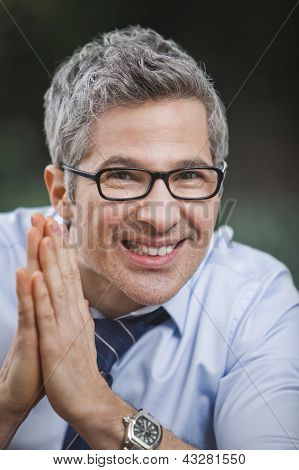 Portrait Of A Businessman Smiling With His Hands Clasped