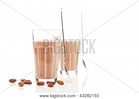 two glasses with chocolate milk and chocolate beans