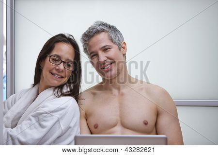 Couple Using A Laptop And Smiling At Home