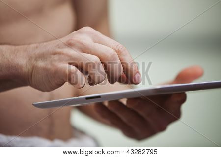 Mid Section View Of A Man Using A Digital Tablet