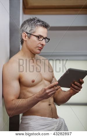 Man standing  Using a Digital Tablet indoors
