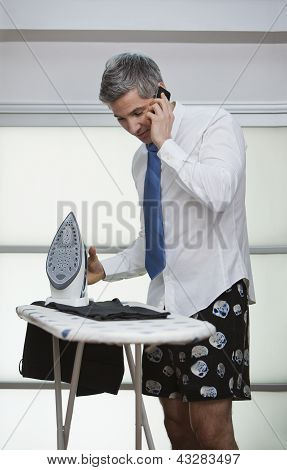 Businessman Talking On A Mobile Phone While Ironing Pants