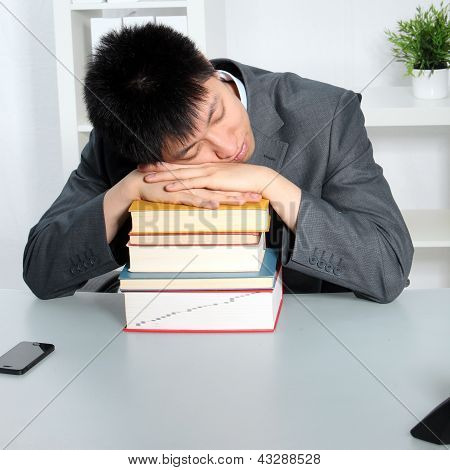Asian Man Sleeping On Top Of A Pile Of Books