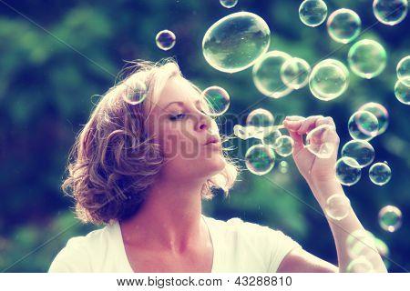 a beautiful woman blowing bubbles