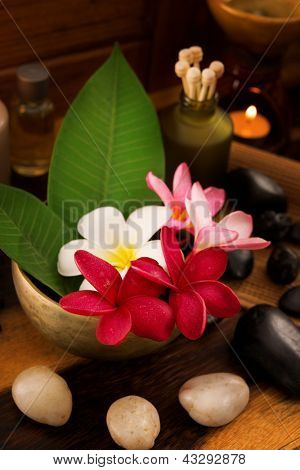 Spa still life setting with aromatic candles, frangipani flower, cold and hot stones.