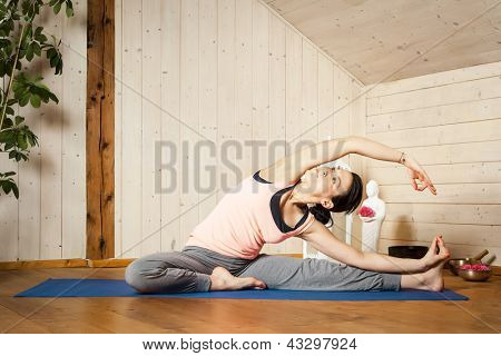 An image of a pretty woman doing yoga at home - Parivrtta Janu Shirshasana