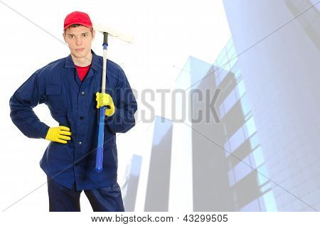 Young Male Window Cleaner With Wiper Over Building With Glass Facade