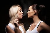 foto of exhale  - Beautiful blonde woman exhaling smoke into face brunette - JPG