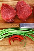 raw fillet chops : fresh beef meat with thyme and red hot dry pepper on wooden plate . isolated over