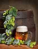 stock photo of bine  - glass of beer with hop cones and old wooden barrel - JPG