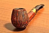 foto of peace-pipe  - Beautiful Carved Pipe On A Wooden Desk - JPG