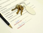foto of rental agreement  - important rental agreement document signed with pen and keys in the background - JPG
