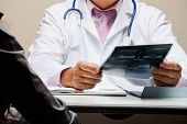stock photo of radiogram  - Midsection of male radiologist at desk holding patient - JPG
