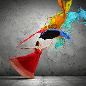 stock photo of dancing rain  - ballet dancer in flying satin dress with umbrella under the paint - JPG