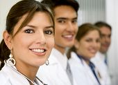picture of medical doctors  - Beautiful female doctor facing the camera with her team behind her - JPG