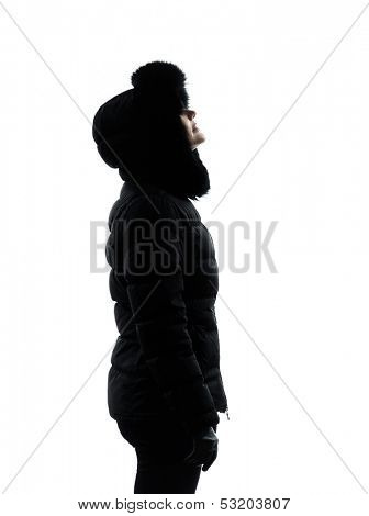 one  woman in winter coat looking up serious silhouette on white background