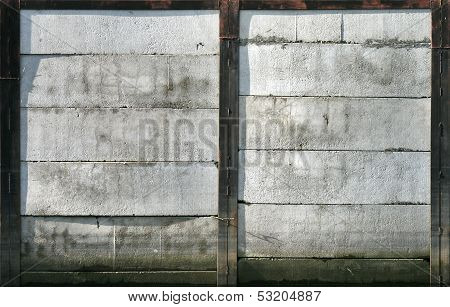 Abstract Texture Of An Old Concrete Mooring Wall With Black Rusted Metal Framing