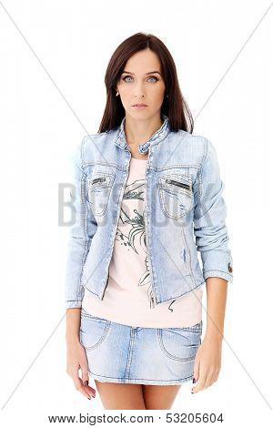 Portrait of a beautiful brunette in jeans jacket and skirt who is posing over a white background