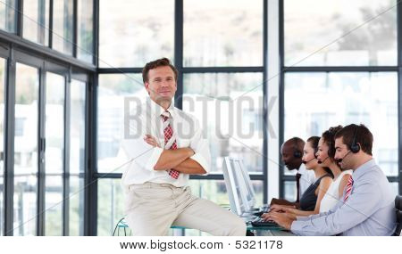 Mature Manager With Folded Arms In A Call Center