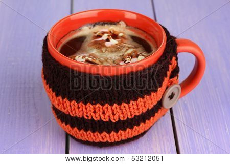 Cup with knitted thing on it on wooden table close up
