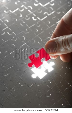 Hand Holding Red Puzzle Piece