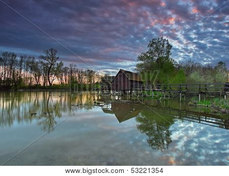 Summer Landscape With River And Watermill With Dramatic Sunset.