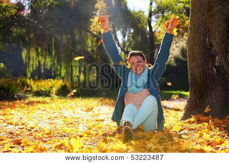 Young Woman Relaxing Playing With Leaves In Autumn Park