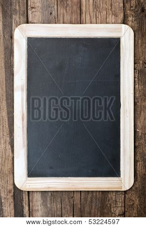 Vintage chalkboard hanging on old wooden background